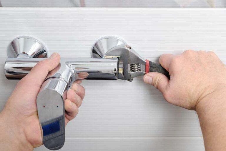 handyman Installing a shower faucet.
